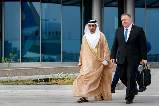 As his plane is reflected in the glass building behind them, Secretary of State Mike Pompeo, right, walks with Abu Dhabi Assistant Foreign Ministry Undersecretary for Protocol Affairs Shihad Al Faheem, as they say goodbye on the secretary's departure from Abu Dhabi, United Arab Emirates, Tuesday, June 25, 2019, en route to an undisclosed location.