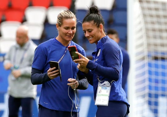 Ashlyn Harris, left, and Ali Krieger chat during a visit to the Parc des Princes stadium in Paris. The couple is planning a December wedding.