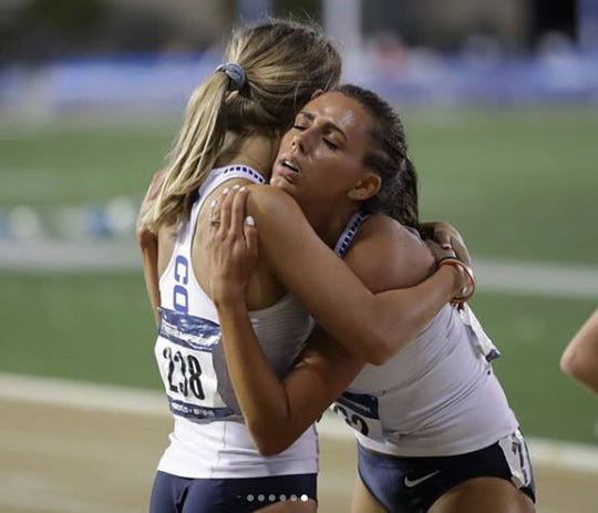 Emma Gee, left, comforts a BYU teammate after a grueling race.