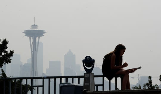 A girl works on a drawing next to an unused viewing scope as a smoky haze obscures the Space Needle and downtown Seattle behind.