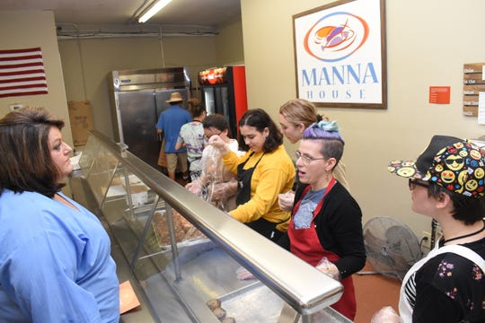 Jessica Viator (left), executive director of the Manna House, talks with Cindy Cooper Blair, education coordinator for the Alexandria Museum of Art. Blair brought members of AMoA's youth group, The Muse, to volunteer at the Manna House which feeds free meals to over 6,500 people a month.