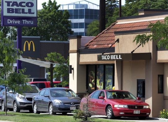 Cars wait in line Wednesday at the Taco Bell on Third Street in Menasha.