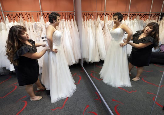 Ann Campeau, left, owner of Strut Bridal, fits a new dress on inventory manager Stefanie Zuniga at her shop in Tempe, Ariz. Cut-rate prices on websites that sell wedding dresses direct from China put pressure on Campeau, who owns four bridal shops in California and Arizona. She has had customers come in after seeing low-end gowns online and expecting to get a dress at a similar price.