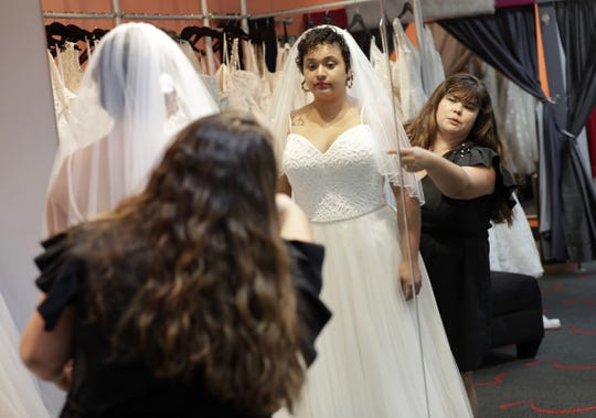 Ann Campeau, right, owner of Strut Bridal, fits a new dress on inventory manager Stefanie Zuniga at her shop in Tempe, Ariz. Cut-rate prices on websites that sell wedding dresses direct from China put pressure on Campeau, who owns four bridal shops in California and Arizona. She has had customers come in after seeing low-end gowns online and expecting to get a dress at a similar price.