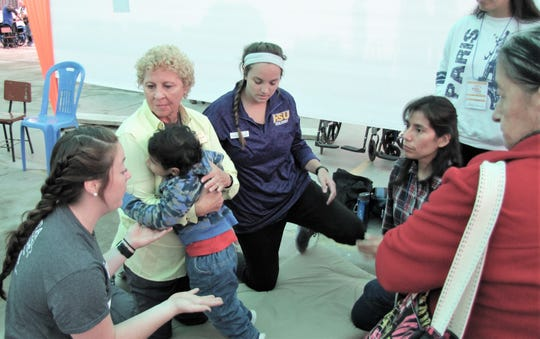 Janelle McConnell, hugging a child, on a Hardin-Simmons summer mission trip for its physical therapy students.