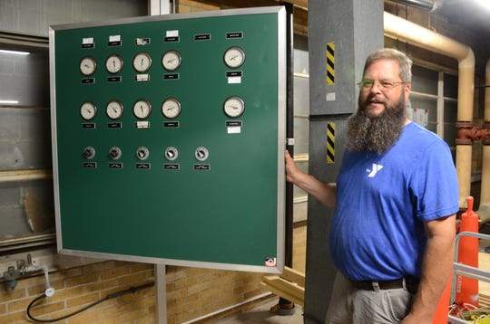 Joe Wright, maintenance supervisor at the YMCA with a control panel from the 1970s.