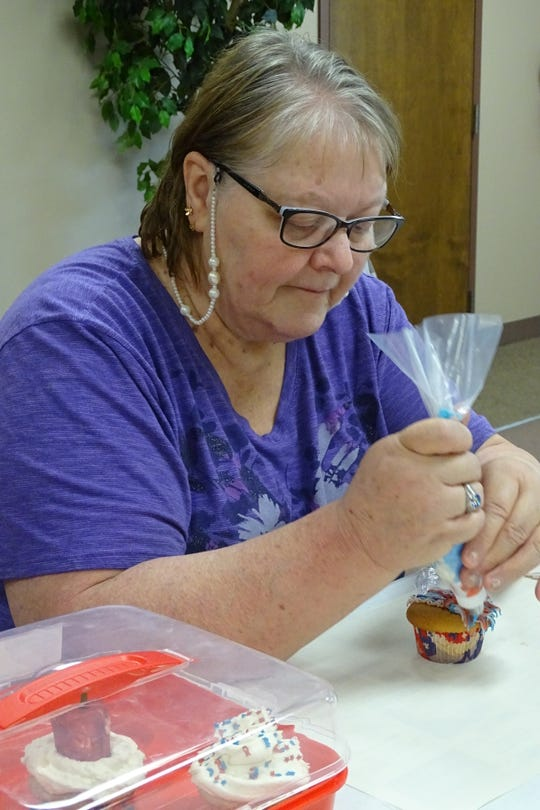 Gloria Pelfrey frosts a cupcake using a grass piping tip during a cupcake decorating class offered Tuesday at the Crawford County Council on Aging.