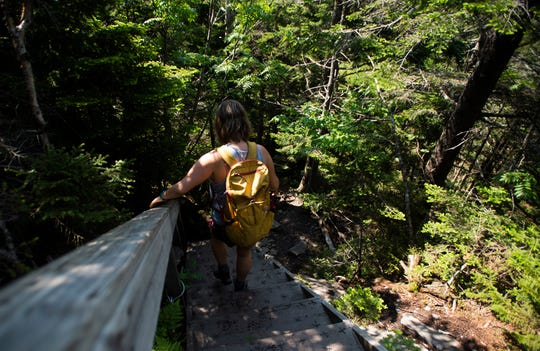 A hiker moves down stairs added to a portion of the trail around Sterling Pond in Jeffersonville, VT, June 23, 2019.