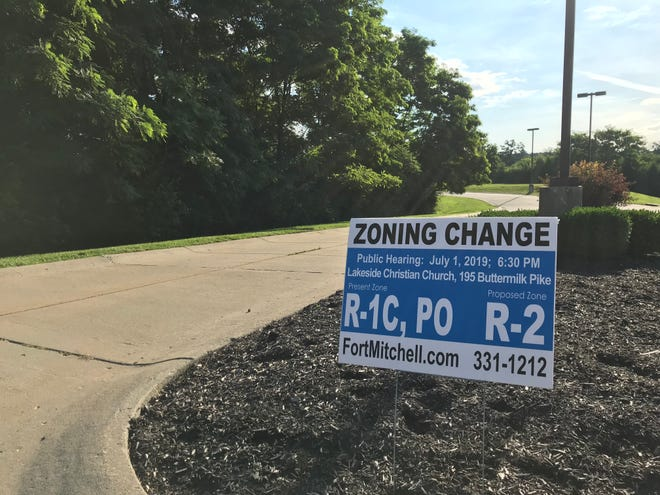 A sign advertises a public hearing on a zoning change that has raised questions about a conflict of interest and the impact on schools.
