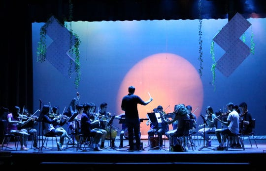 """The Westfield High School Orchestra performs """"Beyond the Gate,"""" composed by Stephanie Ann Boyd, as theater/technology students work behind the scenes to create a compelling light show.  The composer paid a visit to WHS on Friday, May 17, to watch the performance and share feedback."""