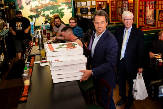 Montana Governor and 2020 Democratic presidential candidate Steve Bullock picks up Fong's pizza to deliver to volunteers at his campaign office who were making calls on Wednesday, June 26, 2019, in Des Moines.