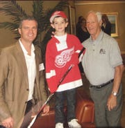A young Ethan Phillips poses between his father, Ash (right) and Gordie Howe.