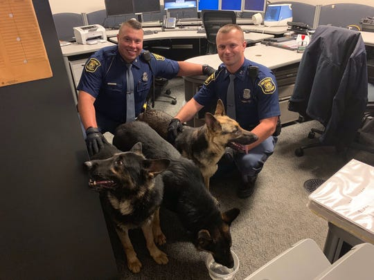Three German Shepherd dogs with Michigan State Police troopers. The dogs were found wandering the freeway on June 26, 2019.