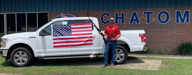 Sales Manager Koby Palmer holds a 12-gauge shotgun and Bible while standing in front of Ford truck draped in an American flag as he poses for a photo as part of Chatom Ford's Fourth of July promotion in Chatom, Alabama.