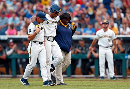Michigan designated hitter Jordan Nwogu (42) is helped of the field after being injured trying to reach first base against Vanderbilt in the third inning of Game 2 of the NCAA College World Series baseball finals in Omaha, Neb., Tuesday, June 25, 2019.