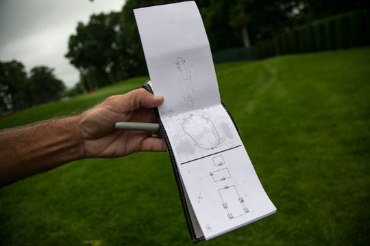 Steve Catlin, caddie for Robert Streb, holds up a yardage book at the ninth green as he maps out the course on foot during practice rounds at Detroit Golf Club on Monday, June 24, 2019.