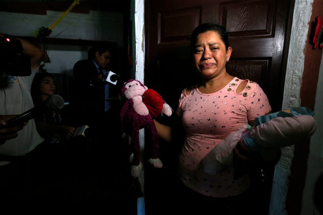 Rosa Ramirez sobs as she shows journalists toys that belonged to her nearly 2-year-old granddaughter Valeria in her home in San Martin, El Salvador.