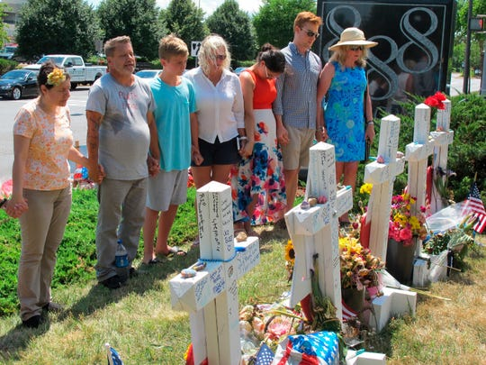 In this July 5, 2018 file photo people pause for a moment of silence next to a memorial near the Capital Gazette building, in Annapolis, Md., for the five Capital Gazette employees who were killed in one of the deadliest attacks on journalists in U.S. history.