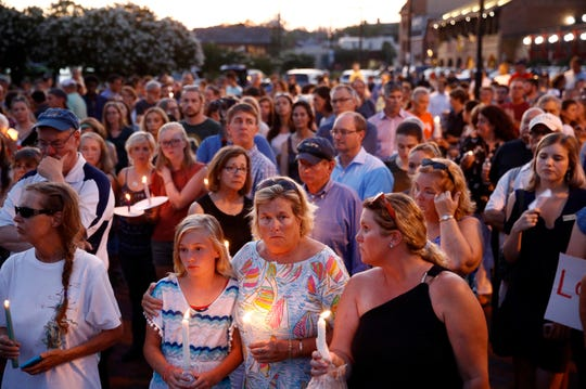 In this June 29, 2018, file photo, mourners stand in silence during a vigil in response to a shooting at the Capital Gazette newsroom, in Annapolis, Md.