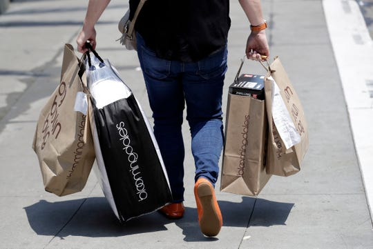 In this July 3, 2018, file photo, a shopper carries bags in San Francisco.