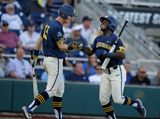 Michigan's Ako Thomas, right, is congratulated by Jimmy Kerr (15) after scoring a run during the first inning on Wednesday.