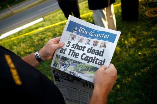 In this June 29, 2018, file photo, Steve Schuh, county executive of Anne Arundel County, holds a copy of the Capital Gazette near the scene of a shooting at the newspaper's office in Annapolis, Md.
