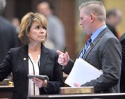 Rep. Lynn Afendoulis, left, talks with Derek Robinson from the House Republican Policy Office during session in The House, Tuesday afternoon, June 18, 2019.