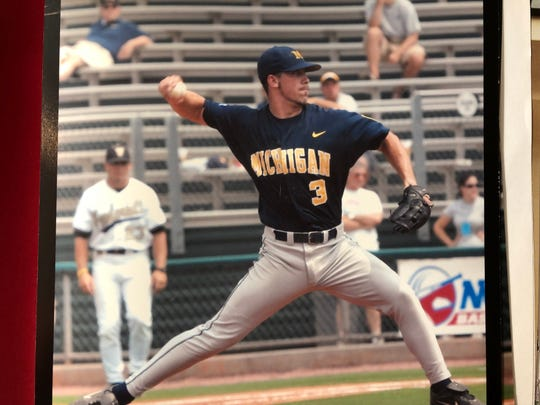 Zach Putnam pitches against Vanderbilt as Erik Bakich coaches first base for the Commodores.