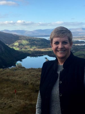 Cyndy Canty stands with her back to the Healy Pass, not far from her cottage in County Cork, Ireland. She says she'll spend additional time in Ireland in retirement.