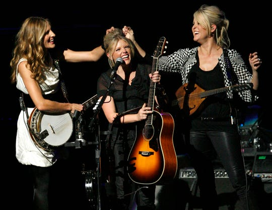 Emily Robison, left, and Martie Maguire, right, adjust Natalie Maines' hair as the Dixie Chicks perform at the Nokia Theatre in Los Angeles in 2007.