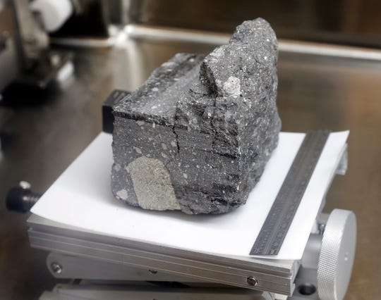 A regolith breccia rock of sintered lunar soil, dating 3.2 billion years old and collected by Apollo 15, is displayed in a pressurized nitrogen-filled case inside the lunar lab at the NASA Johnson Space Center Monday, June 17, 2019, in Houston.