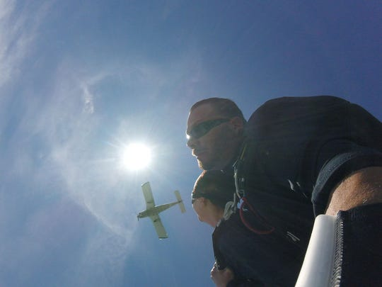 Patty Bauer looks up from her skydive above South Bass Island with instructor JR Piosek.