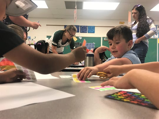 Victor Jurado reaches for a sticker to add to his art project June 26, 2019 with his preschool class. With full-day kindergarten funded by the state, there is some additional money to fund preschool slots.