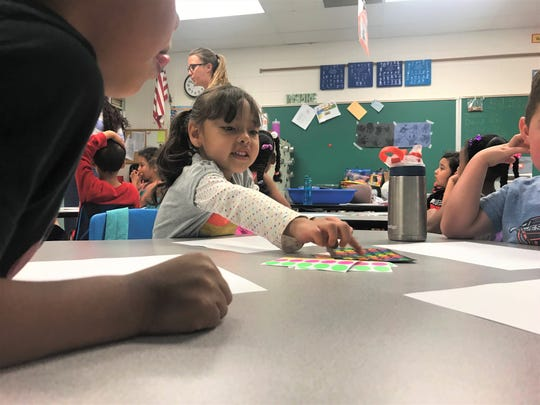 Juliette Diaz Flores reaches for a sticker to add to her art project June 26, 2019 with her preschool class at Bauder Elementary School. Poudre School District has additional preschool slots open for the program.