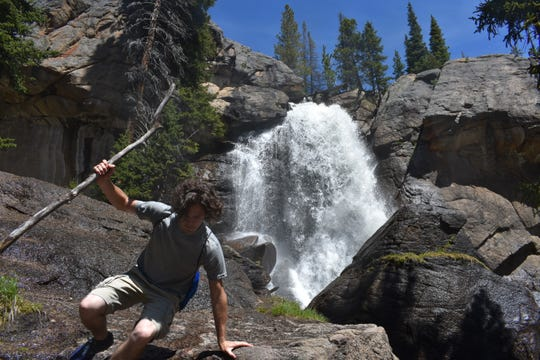 A visitor plays on the boulders below Ouzel Falls in the Wild Basin area of Rocky Mountain National Park.