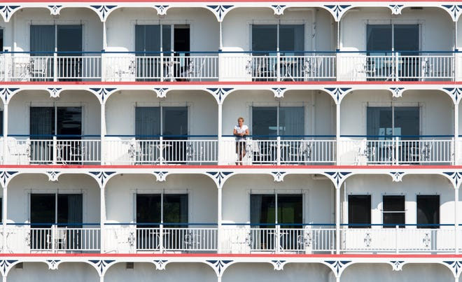 Sarah Acton from Chicago, Ill., looks towards Downtown Henderson from her balcony on board the Queen of the Mississippi as the ship prepares to dock for a visit to Audubon State Park and other local points of interest.