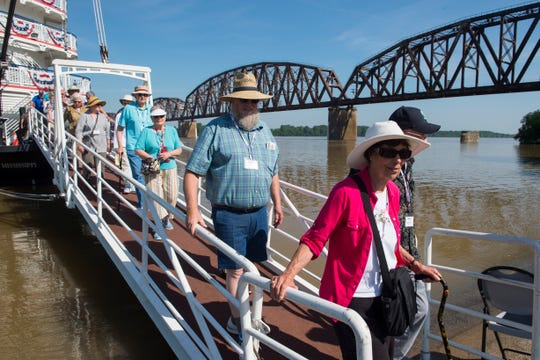 With the CSX railroad bridge in the background, visitors walk the gangway from the Queen of the Mississippi after docking in Downtown Henderson Wednesday morning. Many of the travelers were headed to Audubon State Park for a visit.