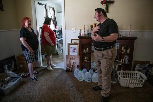 John Hoagland (right) stands near jugs of clean water inside his sister Virginia Ulshafer's (left) rental home in Indianapolis on Wednesday, June 26, 2019.