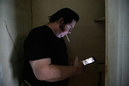 John Hoagland sifts through cellphone photos of the water he and his sister found in her Indianapolis-area rental home. At one point, about a foot or more of water was in the basement, Hoagland said. They only found it after finding a hole in the living room, which does not have working electricity.