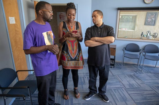 Vernado Malone Sr., (left), Tiana Batiste-Waddell, and Shane Williams look at a local news story involving the shooting of Eric Logan, at the offices of radio station WUBS, South Bend, Tuesday, June 25, 2019. The city, home to Presidential hopeful Pete Buttigieg, is where black resident Eric Logan was recently shot and killed by police, causing some to take issue with the way Buttigieg's administration has handled the shooting and other issues of crime and poverty in the city.