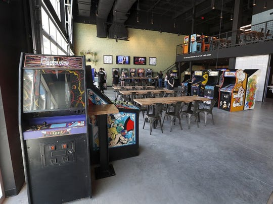 A 1983 Gyruss video games is seen in the foreground at 16-Bit Bar + Arcade, which features dozens of free-to-play games.