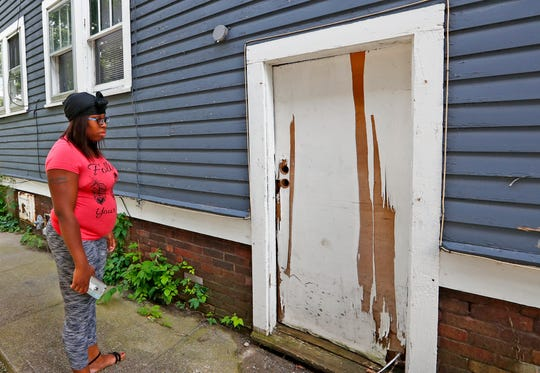 Sherita Sanders stands by a basement door with no lock of a home she used to rent in Indianapolis.
