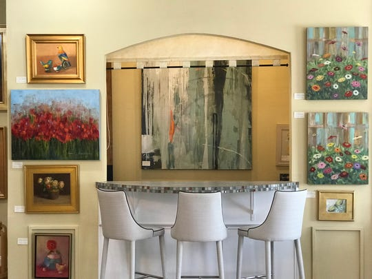 Paintings surround the opening to the kitchen at Jackson Street Gallery in Ridgeland.