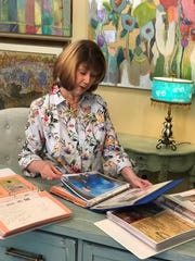 Paula Jackson, owner of Jackson Street Art Gallery, looks through scrapbooks she has filled through the years with information about artists and their exhibits.