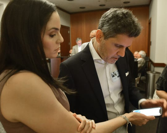 Lauren Hierlmeier and her uncle, attorney John Lauro, review information before attending a meeting of the State and School Employees Health Insurance Management Board.  Hierlmeier's husband, Dr. Bryan Hierlmeier of UMMC, was denied coverage for a cancer treatment by Blue Cross & Blue Shield of Mississippi. Wednesday, June 26, 2019.