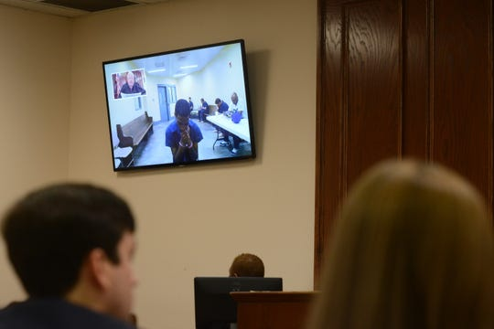 Court officials look toward the screen at Eugene Richmond, 35, as Jackson City Court Judge Blake Anderson reads his charges via video during Richmond's arraignment in Jackson, Tenn., on June 26, 2019.