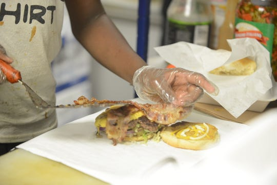 Jacob Richmond Jr. makes a burger at Saucy Jake's Street Food restaurant at 936 Campbell St. on June 1 in Jackson, Tenn.