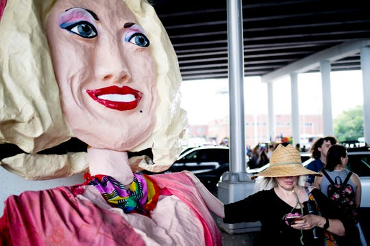 A parade member stands beside a Dolly Parton puppet at the annual Knox Pride Fest Parade in downtown Knoxville, Tennessee on Saturday, June 22, 2019.