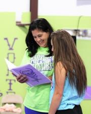 "Twisters Cheer and Tumbling founder Rebekah Chait looks over the schedule with Gibbs High School cheerleader Kaleigh Walton on June 25. ""When I first moved to Knoxville, I taught gymnastics. People would ask me to work with their daughter to get them ready for cheer tryouts,"" said Chait."