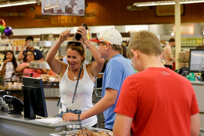 Barbara Holmes of West Lafayette celebrates after receiving her groceries for free during the grand opening of the Fresh Thyme., 2410 N Salisbury st., Wednesday, June 26, 2019 in West Lafayette. Every 100 customers per check-out line received their groceries on the store.